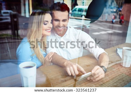 Happy couple at cafe using smartphone - stock photo