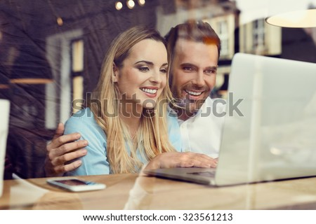 Happy couple at coffee shop looking at laptop - stock photo