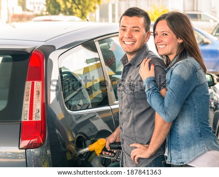 Happy couple at fuel station pumping gasoline at gas pump. Portrait of young man and woman of man filling modern car at gasoline tank. - stock photo
