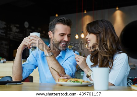 Happy couple at restaurant eating lunch, having fun - stock photo