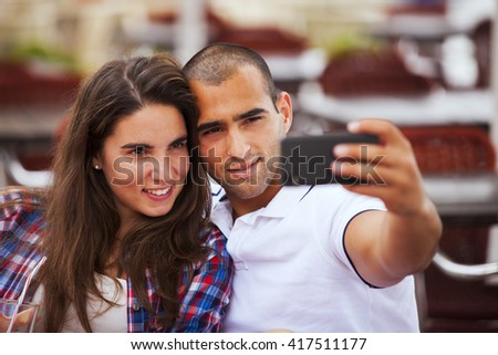 Happy couple at the bar making selfies - stock photo