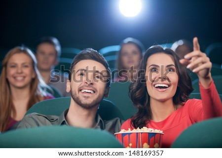Happy couple at the cinema. Cheerful young couple watching movie at the cinema - stock photo