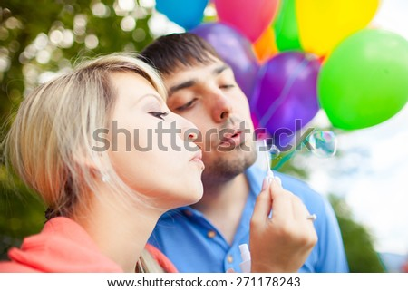 Happy couple blowing bubbles at a park. - stock photo
