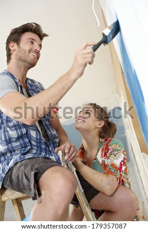 Happy couple building new home, painting wall, smiling. - stock photo
