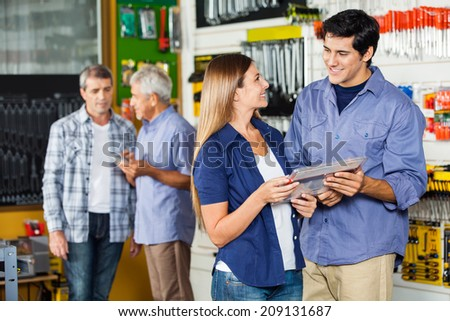 Happy couple buying tool set at hardware store with customers in background - stock photo