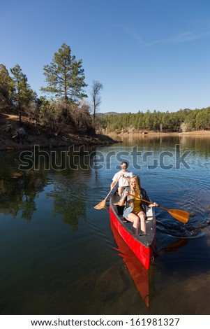 Happy Couple Canoeing on a Calm Lake - stock photo