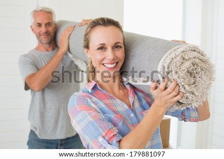 Happy couple carrying a rolled up rug together in their new home - stock photo
