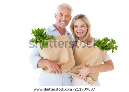 Happy couple carrying paper grocery bags on white background - stock photo