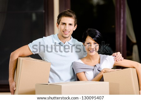 Happy couple carrying pasteboard boxes while moving to new house - stock photo