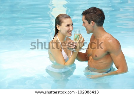 Happy couple celebrating with sparkling wine in swimming pool - stock photo