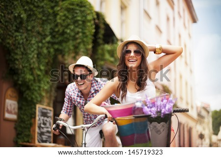 Happy couple chasing each other on bike - stock photo