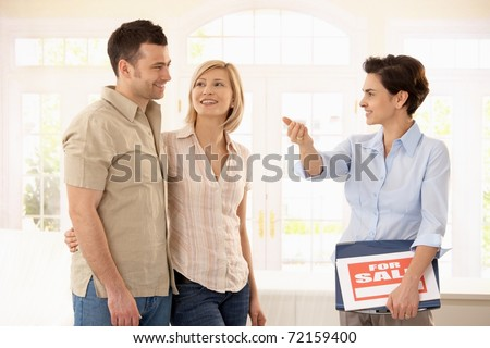 Happy couple checking new house with estate agent.? - stock photo