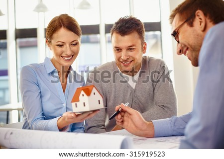 Happy couple choosing new home design with architect - stock photo