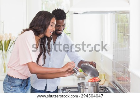 Happy couple cooking food together at home in the kitchen - stock photo