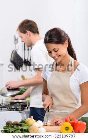 Happy couple cooking in the kitchen, beautiful wife slicing vegetables - stock photo