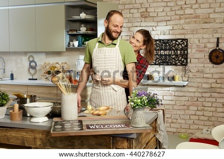Happy couple cooking together in kitchen, woman tieing apron on man. - stock photo