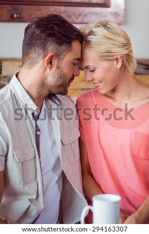Happy couple cuddling on the sofa at home - stock photo