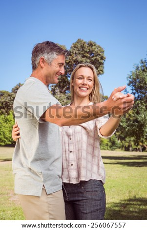 Happy couple dancing in the park on a sunny day - stock photo