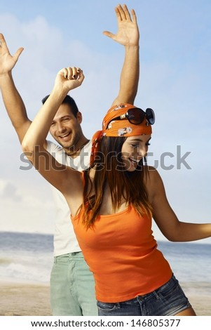 Happy couple dancing on the beach at summertime, having fun. - stock photo