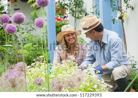 Happy couple doing the gardening at home - stock photo
