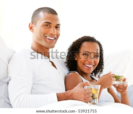 Happy couple drinking a cup of tea lying on their bed at home - stock photo