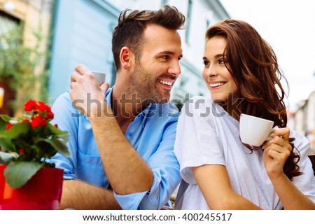 Happy couple drinking coffee in outdoors cafe on summer vacation - stock photo