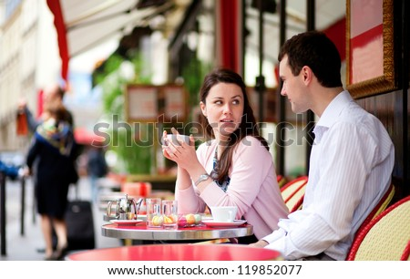 Happy couple drinking coffee or tea in a Parisian outdoor cafe - stock photo