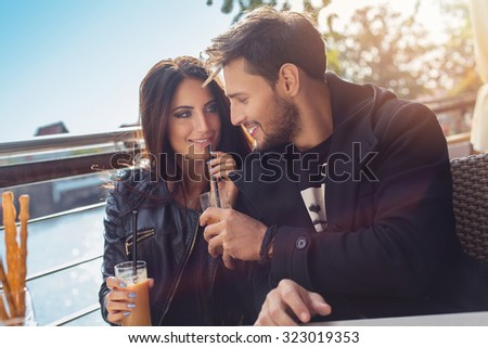 Happy couple drinking orange juice in autumn time - stock photo