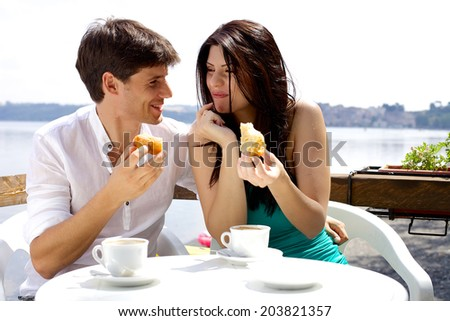 Happy couple eating cake in hotel in front of lake in Italy - stock photo