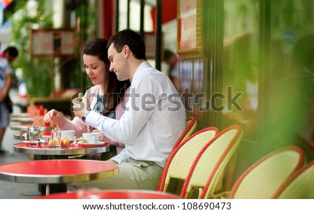 Happy couple eating macaroons in a Parisian outdoor cafe - stock photo