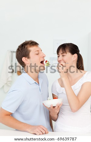 Happy couple eating together in the kitchen - stock photo