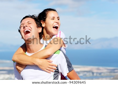 Happy couple embrace each other and laugh together outdoors in a healthy relationship outdoors concept - stock photo
