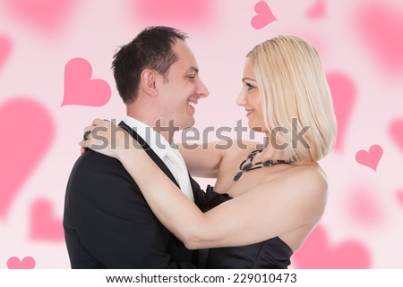 Happy couple embracing amidst hearts over colored background - stock photo
