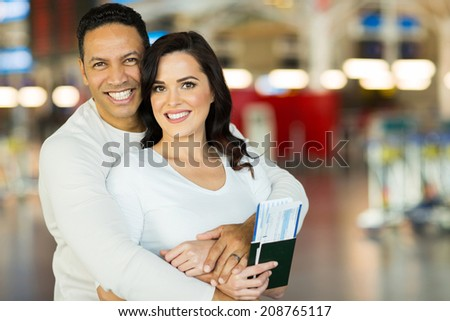 happy couple embracing at airport - stock photo