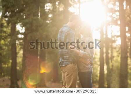 Happy couple embracing at sunset in the nature - stock photo