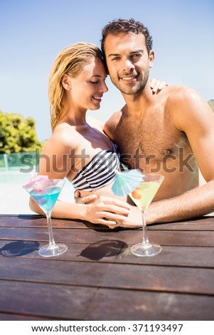 Happy couple embracing in the pool with cocktails on the pool edge - stock photo