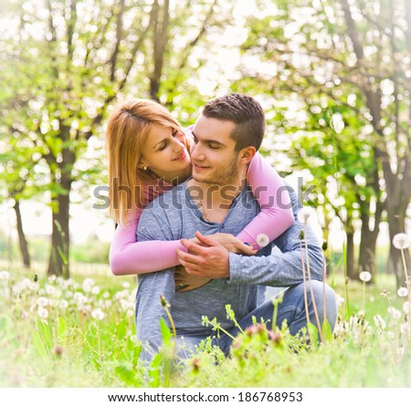 Happy couple embracing outdoor in park. Soft light. - stock photo