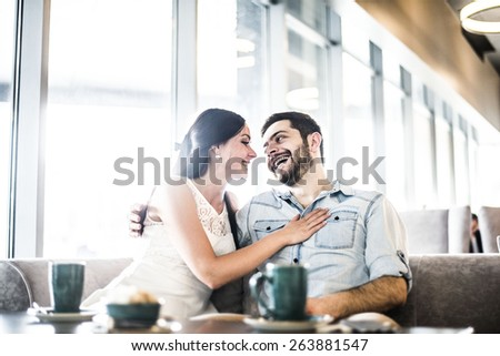 Happy couple enjoy coffee at coffee shop cafe Young adult man and woman kiss touch nose each other against window glass in perspective Romantic relationship Pair embrace and look each other - stock photo
