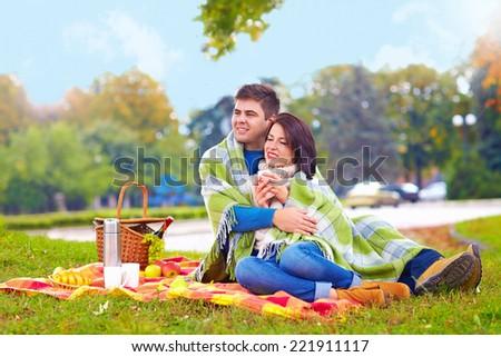 happy couple enjoying autumn picnic in city park - stock photo