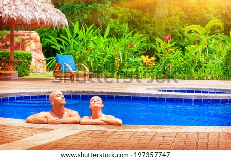 Happy couple enjoying pool, young family on day spa relaxation, luxury vacation on tropical resort, romantic travel destination  - stock photo