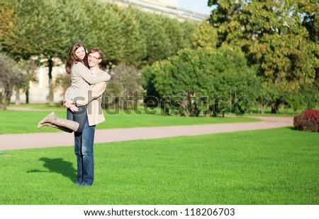 Happy couple enjoying sunny autumn day in park - stock photo