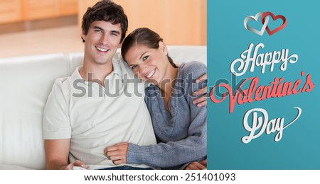 Happy couple enjoying their time together on the couch against cute valentines message - stock photo