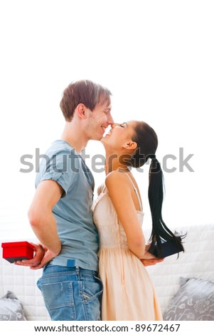 Happy couple exchanging gifts - stock photo