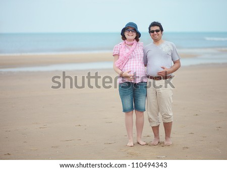 Happy couple expecting child, having vacation at seaside - stock photo