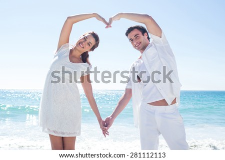 Happy couple forming heart shape with their hands at the beach - stock photo