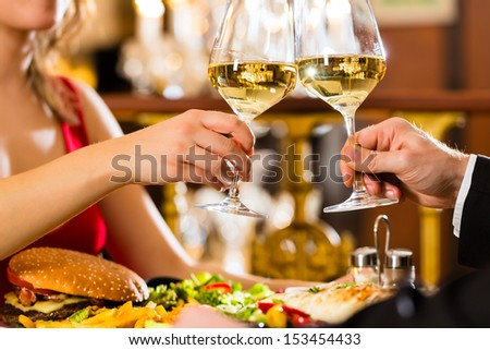 happy couple have a romantic date in a fine dining restaurant they drink wine and clinking glasses, cheers - a large chandelier is in Background - stock photo