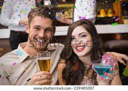 Happy couple having a drink together against flying colours - stock photo