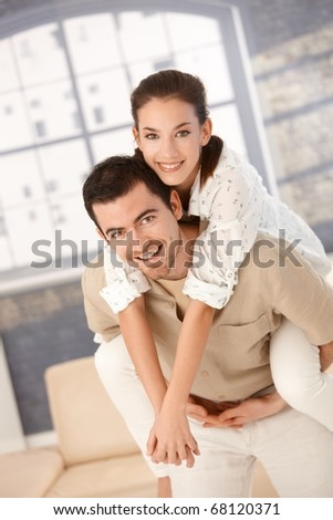 Happy couple having fun at home, man holding woman on his back, smiling. - stock photo