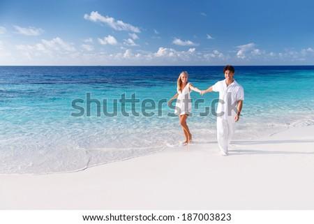 Happy couple having fun on the beach, spending honeymoon on luxury tropical resort, summer holidays, love concept  - stock photo