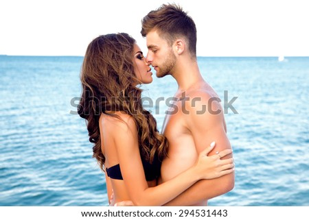 Happy Couple having fun on the Beach.Summer Vacation.Attractive Man and Woman at Beach.handsome boyfriend,sensual couple,lovers,sea background,happiness,couple kissing,teen people travel,beach,love - stock photo